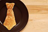 Father's day background image with real pancake in the shape of a necktie on plate.  Closeup with wo