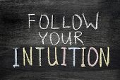 stock photo of intuition  - follow your intuition phrase handwritten on blackboard - JPG