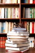 foto of education  - Eyeglasses lying on the opened book and many other books on background - JPG