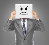 picture of face mask  - businessman covering his face with angry mask on gray background - JPG