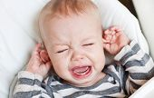 stock photo of love hurts  - cute little boy crying and holding his ear on a white background - JPG