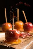 Group of toffee apples on rustic wooden board