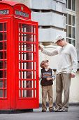 pic of phone-booth  - Happy father and son outdoors in city by red phone booth - JPG