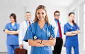stock photo of male nurses  - Portrait of a nurse in front of her medical team - JPG