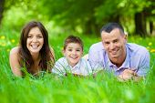 stock photo of lie  - Happy family of three lying on grass while reading book - JPG