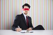 stock photo of blindfolded man  - Blindfold businessman at his office signing contracts - JPG