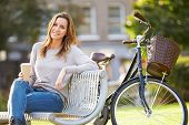 picture of takeaway  - Woman Relaxing On Park Bench With Takeaway Coffee - JPG