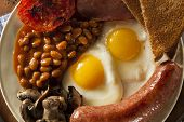 stock photo of yolk  - Traditional Full English Breakfast with Eggs Bacon Sausage and Baked Beans - JPG