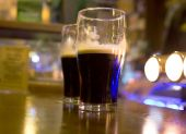 stock photo of guinness  - Two half full stout beers on a bar - JPG