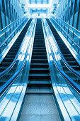 image of escalator  - escalator in blue two tone color going up stairs in building - JPG