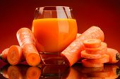 picture of carrot  - Carrot juice and slices of carrot on a orange background - JPG