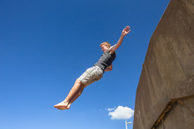 image of parkour  - Teen boy jumping off wall somersault in blue sky in parkour on beach - JPG