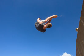 picture of parkour  - Teen boy jumping off wall somersault in blue sky in parkour on beach - JPG