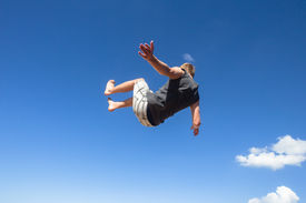 stock photo of parkour  - Teen boy jumping off wall somersault in blue sky in parkour on beach - JPG