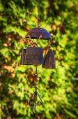 foto of windchime  - Made of copper antique wind chime in the autumnal sunshine - JPG