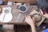 stock photo of guitar  - luthier making a guitar rosette over a desk with the cover of the guitar beside him at the workshop - JPG