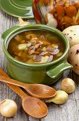 picture of chanterelle mushroom  - Delicious Vegetarian Soup with Chanterelle Mushrooms in Green Pot with Raw Potato Onion Marinated Mushrooms and Wooden Spoons on closeup Rustic Wooden background - JPG