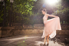 stock photo of ballerina  - Young beautiful ballerina with pink dress dancing. Outdoor portrait ** Note: Soft Focus at 100%, best at smaller sizes - JPG
