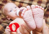 image of child feeding  - beautiful little baby drinking tea or juice from bottle - JPG