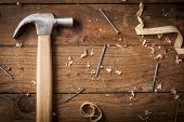 image of carpenter  - carpenter hammer nail and shavings on wooden surface - JPG