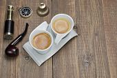 picture of spyglass  - Spyglass Compass Smoking Pipe and Two White Espresso Coffee Cups On Grunge Wooden Table - JPG