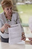 picture of divorce-papers  - Retired woman giving husband divorce decree paper  - JPG
