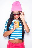 picture of orange-juice  - Attractive young African woman in funky clothes drinking orange juice and looking at camera while standing against white background - JPG