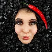 stock photo of licorice  - Beautiful woman face with licorice and chili frame - JPG