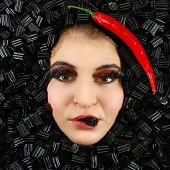 foto of licorice  - Beautiful woman face with licorice and chili frame - JPG
