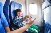picture of jet  - Little boy takes little plane from moms hand sitting by the window in jet airplane - JPG