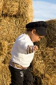 stock photo of haystack  - Country boy in national costume plays in a haystack - JPG
