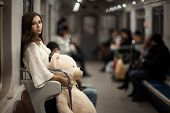 stock photo of not found  - Sad girl with toy bear in her hands she in a subway car - JPG