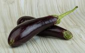 picture of aubergines  - Fresh bright raw Aubergines on the wooden background - JPG