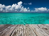 picture of crystal clear  - Crystal clear turquoise water and old wooden pier at tropical maldivian beach - JPG