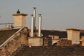 stock photo of roof-light  - Chimneys on roofs in late afternoon light - JPG