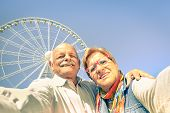 Постер, плакат: Happy Retired Senior Couple Taking Selfie At Travel Around The World Active Playful Elderly