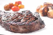 picture of rib eye steak  - barbequed beef rib steak grilled to perfection with salad and potato - JPG