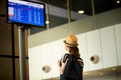 stock photo of carry-on luggage  - Young woman in 20s in straw hat and summer dress with carry - JPG