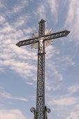 foto of wrought iron  - Wrought iron cross with Jesus against blue sky - JPG