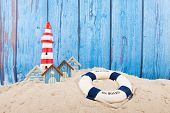 picture of lighthouse  - Beach with lighthouse and life buoy in front of vintage blue background - JPG