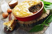 stock photo of nettle  - Pie nettles rice and canned fish on the table - JPG