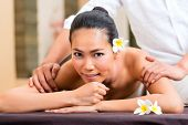 stock photo of massage oil  - Indonesian Asian woman in wellness beauty day spa having aroma therapy massage with essential oil - JPG