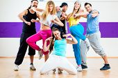 picture of zumba  - Young men and women dancing zumba modern group choreography in dance school - JPG