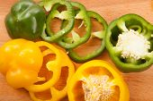 stock photo of yellow-pepper  - Cutted yellow and green bell peppers on wooden cutting board - JPG