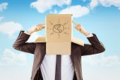 picture of anonymous  - Anonymous businessman pointing to box against blue sky - JPG
