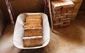 stock photo of wheelbarrow  - Wheelbarrow full of bricks in an unfinished ecological house - JPG