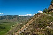 image of vegetation  - Scenic top view on the valley between the mountains road hills covered with vegetation forest blue sky and clouds - JPG