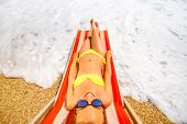 image of sunbather  - Young and beautiful woman relaxing and having sunbath on the red sunbed in the sea - JPG