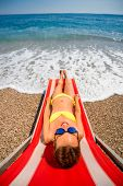 stock photo of sunbather  - Young and beautiful woman relaxing and having sunbath on the red sunbed in the sea - JPG