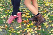 stock photo of dry grass  - Legs and shoes of young girls standing on the dry leaves and grass on beautiful autumn day - JPG